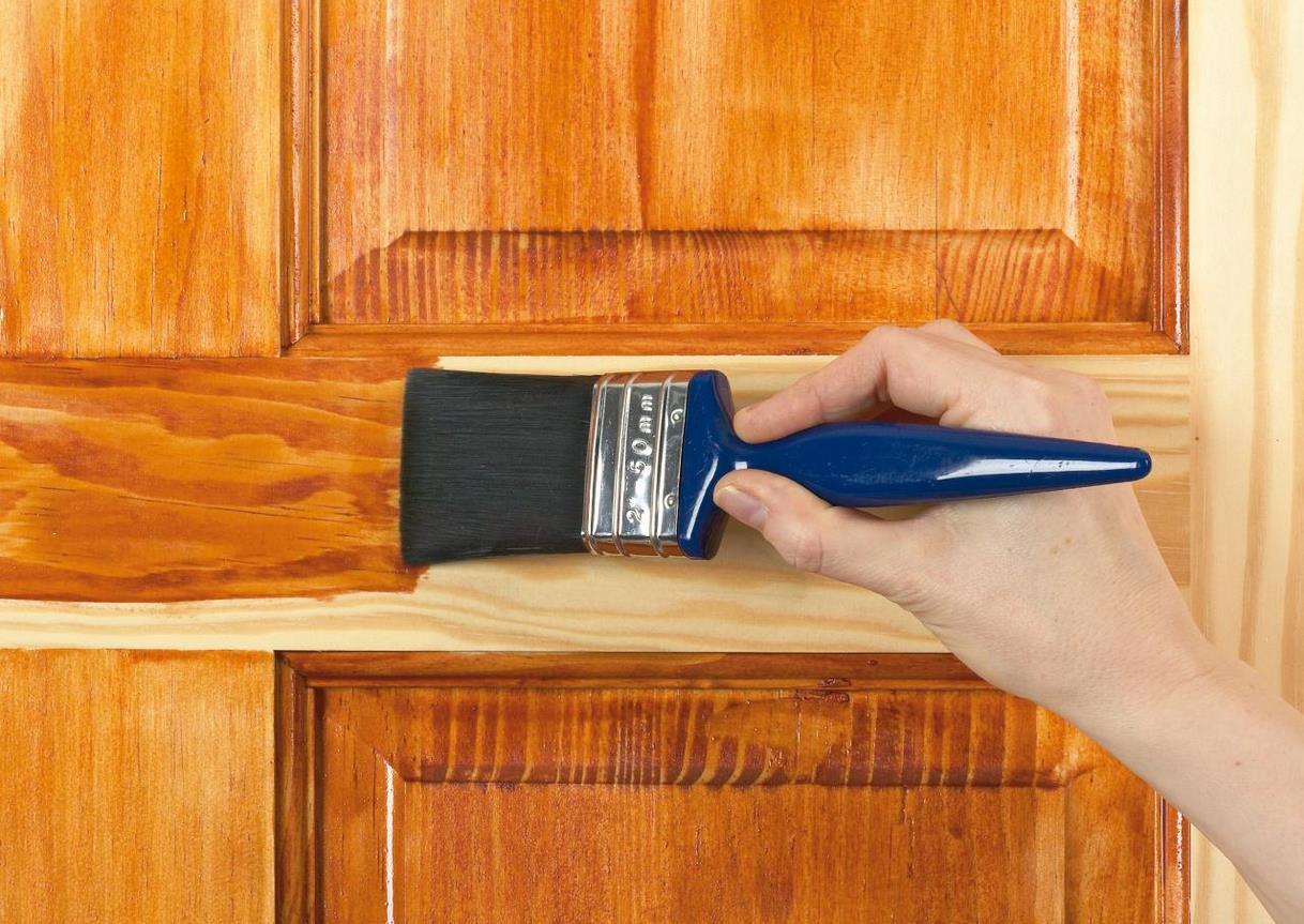 Фото: нанесение лака на деревянную дверь